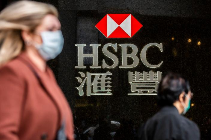 A woman (L) walks past a HSBC sign in Hong Kong on February 18, 2020. - The London-based, Asia-focused behemoth HSBC is expected to release its Q4 and 2019 results later on February 18. (Photo by ISAAC LAWRENCE / AFP) (Photo by ISAAC LAWRENCE/AFP via Getty Images)
