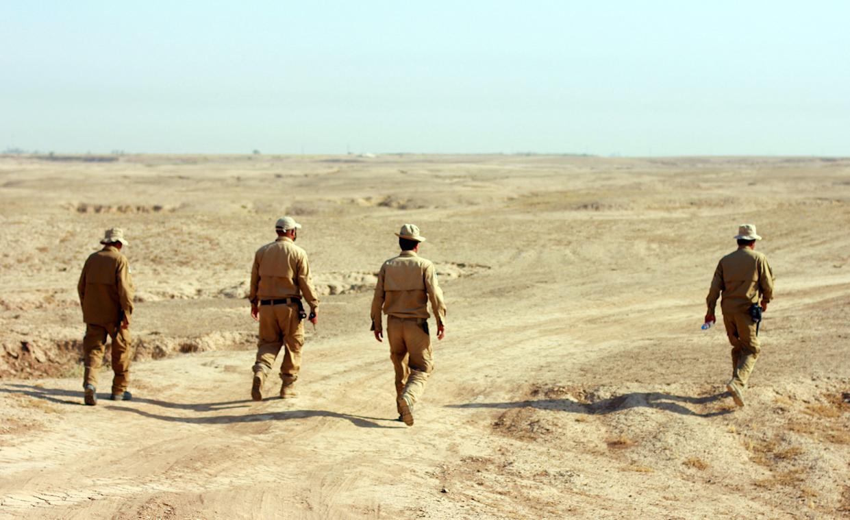 The FSD's Team 1 walks out among the trenches behind the frontlines, where Peshmerga have set up fortified hills, to prepare for a detonation that will destroy explosives left behind by ISIS. (Photo: Ash Gallagher for Yahoo News)