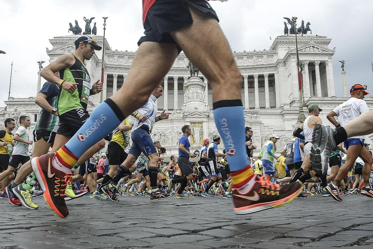 <p>Participants pass the Monument for Italian King Viktor Emmanuel II on Piazza Venezia in Rome during the 23rd edition of the Rome Marathon. (Photo: Giuseppe Lami/EPA) </p>