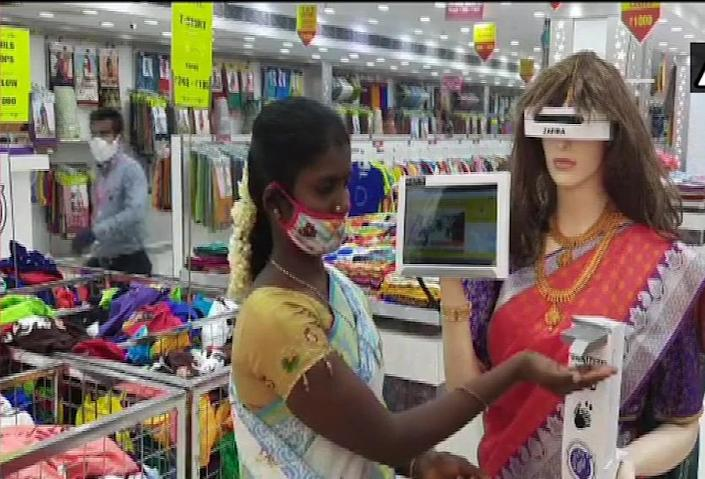 Zafira, the humanoid, checks temperature and dispenses hand sanitizers to customers at garment stores. (Image courtesy: ANI)