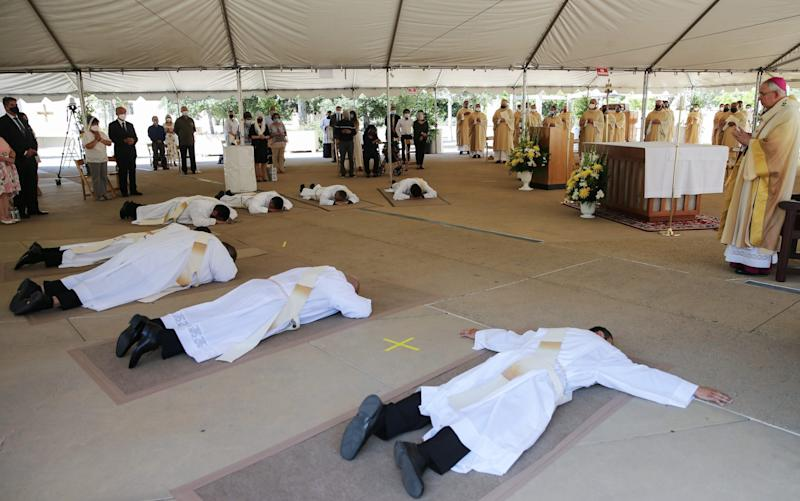 Candidates for priesthood lie prostrate during the first-ever outdoor Ordination Mass at the Cathedral of Our Lady of the Angels amid the Covid-19 pandemic -  Mario Tama/Getty Images