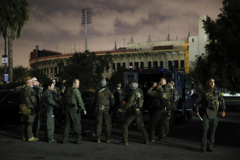 ATF agents gather for a briefing in the parking lot of the Los Angeles Memorial Coliseum early Wednesday morning, May 17, 2017, in Los Angeles. Hundreds of federal and local law enforcement fanned out across Los Angeles, serving arrest and search warrants as part of a three-year investigation into the violent and brutal street gang MS-13. (AP Photo/Jae C. Hong)