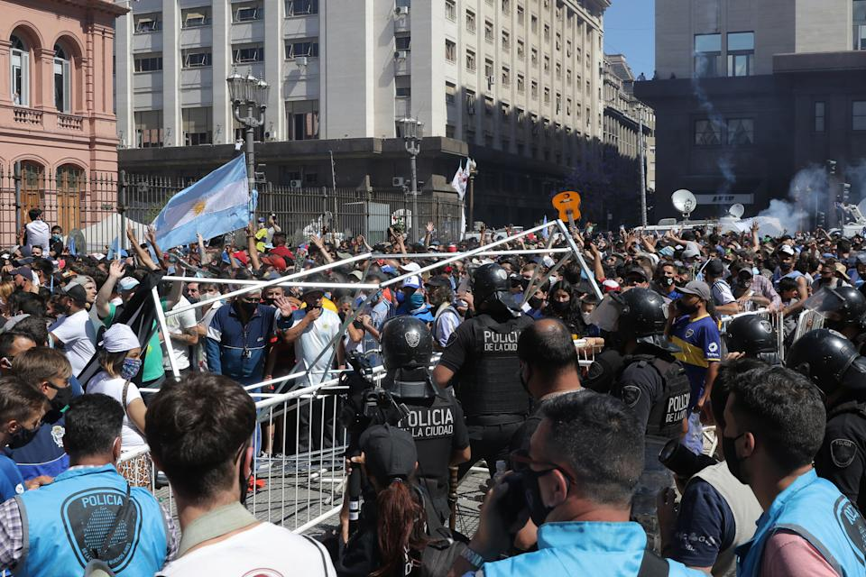 BUENOS AIRES, ARGENTINA - NOVEMBER 26: Police officers try to contain riots as fans tried to climb over the fence to enter Casa Rosada during Diego Maradona's funeral on November 26, 2020 in Buenos Aires, Argentina. Maradona died of a heart attack at his home on Thursday 25 aged 60 . He is considered among the best footballers in history and lead his national team to the World Cup in 1986. President of Argentina Alberto Fernandez declared three days of national mourning. (Photo by Federico Peretti/Getty Images)