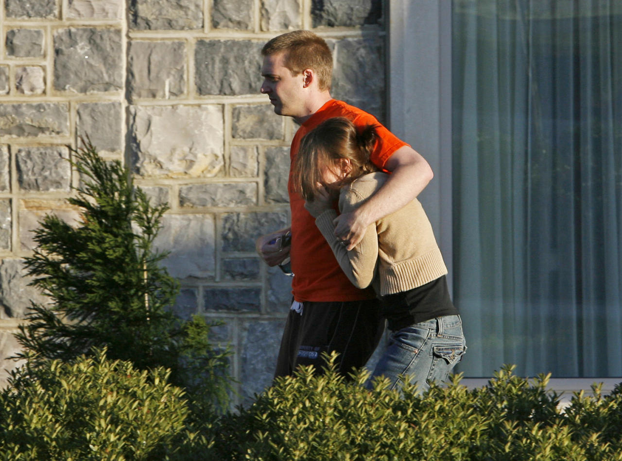 <p>An unidentified couple leaves The Inn on the campus of Virginia Tech in Blacksburg, Va., Monday, April 16, 2007, following a shooting rampage at the school that left 33 people dead including the suspect. The Inn was used as a meeting point for friends and family awaiting word on loved ones. (Photo: Mark Gormus/Richmond Times-Dispatch/AP) </p>