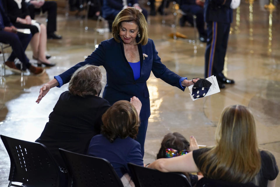 """House Speaker Nancy Pelosi of Calif., greets the family of slain U.S. Capitol Police officer William """"Billy"""" Evans, including Janice Evans, from left, Logan Evans, Abigail Evans, and Shannon Terranova, during a ceremony in the Rotunda at the Capitol in Washington, Tuesday, April 13, 2021. (AP Photo/J. Scott Applewhite, Pool)"""