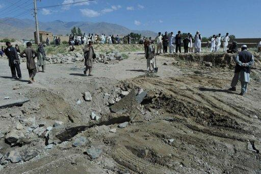 Villagers look at a crater at the scene where a civilian minibus was hit by a remote-controlled bomb in Kabul on August 7, 2012. The Taliban attack killed eight people and wounded five when it struck a minibus in Kabul, police said, amid growing unrest in areas neighbouring the Afghan capital