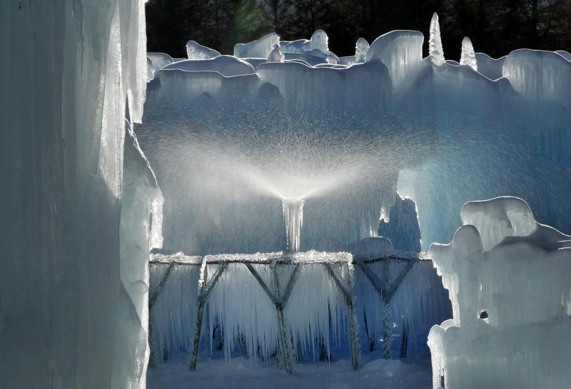 In this Monday, Jan. 28, 2019 photo, a sprinkler sprays a fine mist over a metal rack to grow icicles at Ice Castles in North Woodstock, N.H. Ice artists will harvest the icicles and use them to grow the castles' walls. (AP Photo/Robert F. Bukaty)