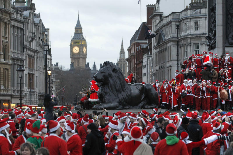 FILE. In this Dec. 15, 2012 file photo, revellers dressed up in Santa gather at Trafalgar Square in London during a SantaCon festival in London. SantaCon events unfold in more than 300 cities worldwide and the New York celebration is one of the biggest, but complaints about boorish, bar-hopping St. Nicks at previous SantaCons got attention from local officials and the NYPD. (AP Photo/Sang Tan, File)
