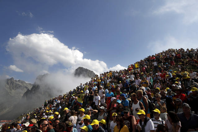 Spectators stand on the Tourmalet pass next to the finish line of the fourteenth stage of the Tour de France cycling race over 117.5 kilometers (73 miles) with start in Tarbes and finish at the Tourmalet pass, France, Saturday, July 20, 2019. (AP Photo/ Christophe Ena)