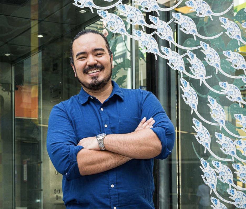 MasterChef season two winner Adam Liaw wears a blue shirt and poses in front of a glass door