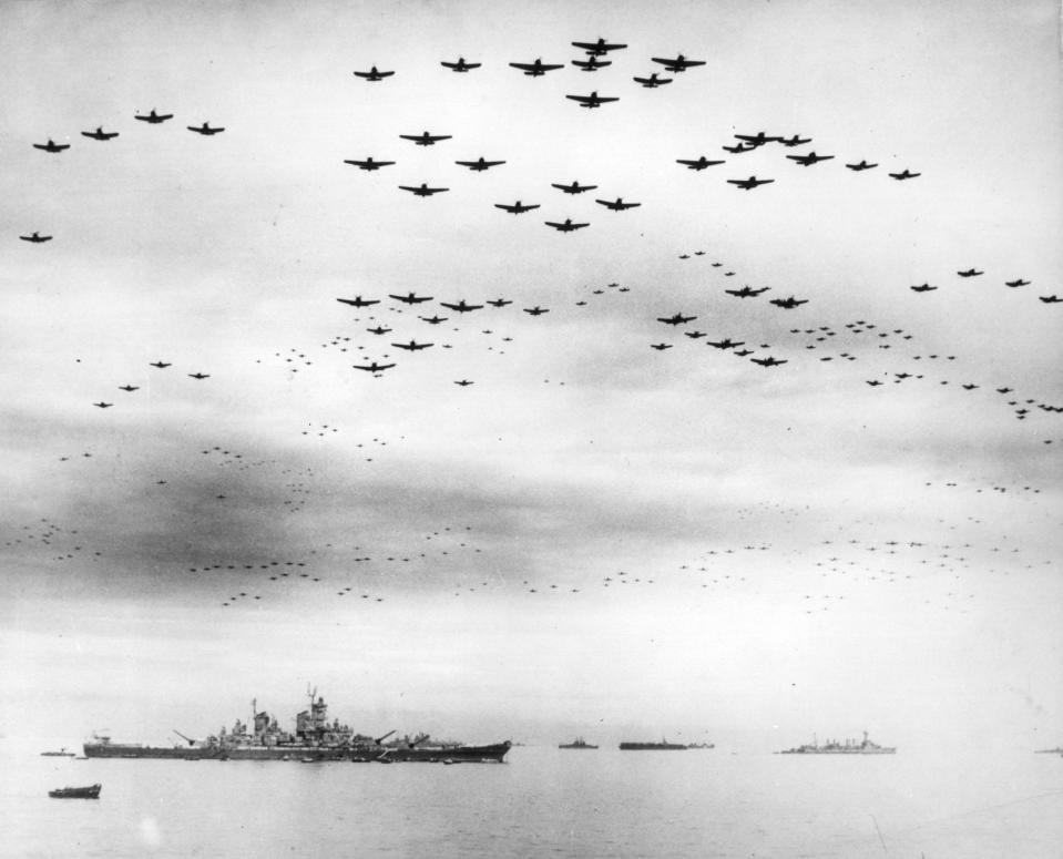 FILE - In this image provided by the U.S. Navy, fighter planes fly in formation over the USS Missouri, while the surrender ceremonies to end World War II take place aboard the U.S. Navy battleship, on Sept. 2, 1945. Several dozen aging U.S. veterans, including some who were in Tokyo Bay that day, will gather in Pearl Harbor in September to mark the 75th anniversary of Japan's surrender, even if it means the vulnerable group may be risking their lives again amid the coronavirus pandemic. (U.S. Navy via AP, File)