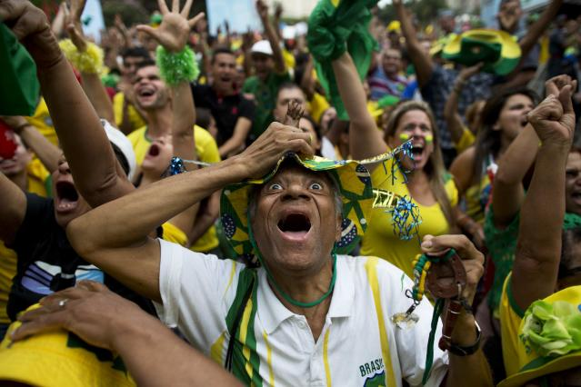 Brazil fans celebrate after their team defeated Chile during a live broadcast of the World Cup round of 16 match inside the FIFA Fan Fest area in Sao Paulo, Brazil, Saturday, June 28, 2014. (AP Photo/Rodrigo Abd)