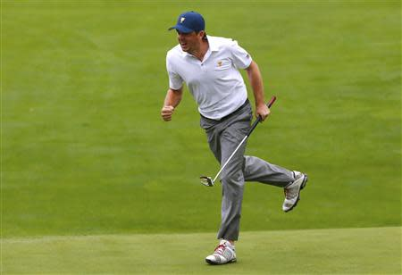 Keegan Bradley of the U.S. celebrates after sinking his putt on the 18th hole while playing Justin Day of Australia and Graham DeLaet of Canada during the continuation of the rain delayed Foursome matches for the 2013 Presidents Cup golf tournament at Muirfield Village Golf Club in Dublin, Ohio October 6, 2013. REUTERS/Jeff Haynes