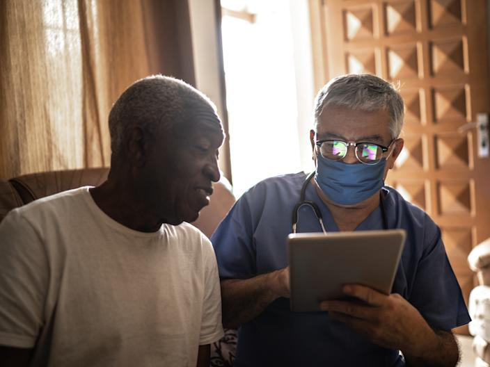 A stock photo of a black patient with a doctor.