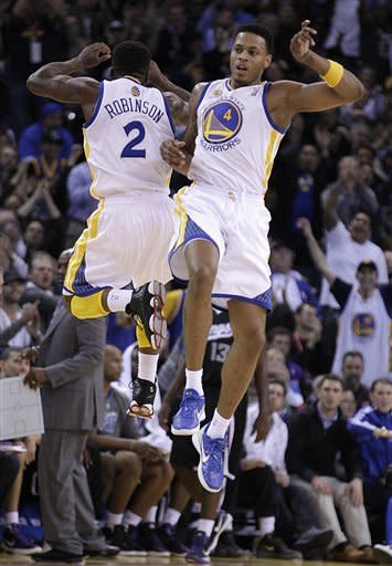 Golden State Warriors' Brandon Rush, right, and Nate Robinson (2) celebrate in the final minutes of the NBA basketball game against the Sacramento Kings Tuesday, Jan. 31, 2012, in Oakland, Calif. (AP Photo/Ben Margot)