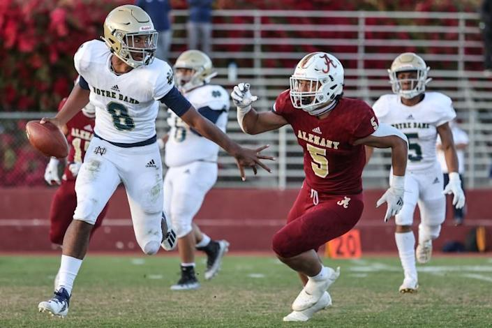 Mission Hills, CA, Friday, March 19, 2021 - Sherman Oaks Notre Dame quarterback Javance Tupouata-johnson is chased by Bishop Alemany linebacker Niuafe Jr Tuihalamaka during second half action at Alemany. (Robert Gauthier/Los Angeles Times)