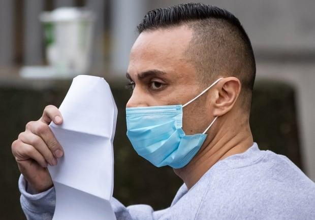 Mohammad Movassaghi tries to hide his face with a copy of his release order after getting out on bail in January. Movassaghi later pleaded guilty to violating public health orders. (Canadian Press - image credit)