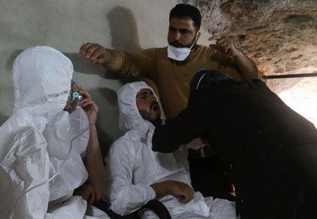 A man breathes through an oxygen mask as another one receives treatments, after what rescue workers described as a suspected gas attack in the town of Khan Sheikhoun in rebel-held Idlib, Syria April 4, 2017. REUTERS/Ammar Abdullah