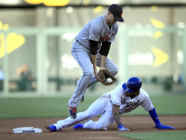 Kansas City Royals' Adalberto Mondesi, bottom, beats the tag by Detroit Tigers shortstop Jordy Mercer, top, during the first inning of a baseball game at Kauffman Stadium in Kansas City, Mo., Friday, July 12, 2019. Mondesi was safe with a stolen base on the play. (AP Photo/Orlin Wagner)