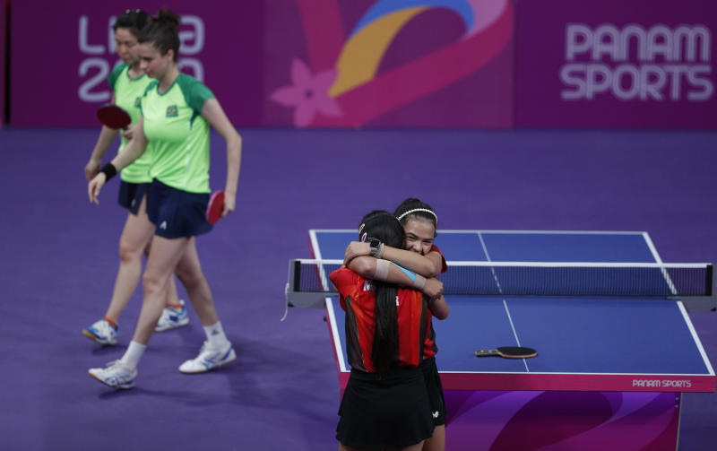 Adriana Diaz, right, and Melanie Diaz, of Puerto Rico, hug after defeating Bruna Takahasi and Jessica Yamada of Brazil in a women's doubles table tennis semifinal at the Pan American Games in Lima, Peru, Monday, Aug. 5, 2019. (AP Photo/Rebecca Blackwell)