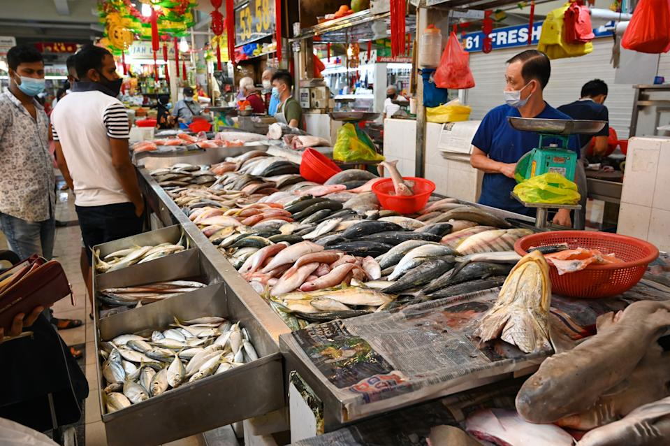 People shop for fish at a wet market in Singapore.