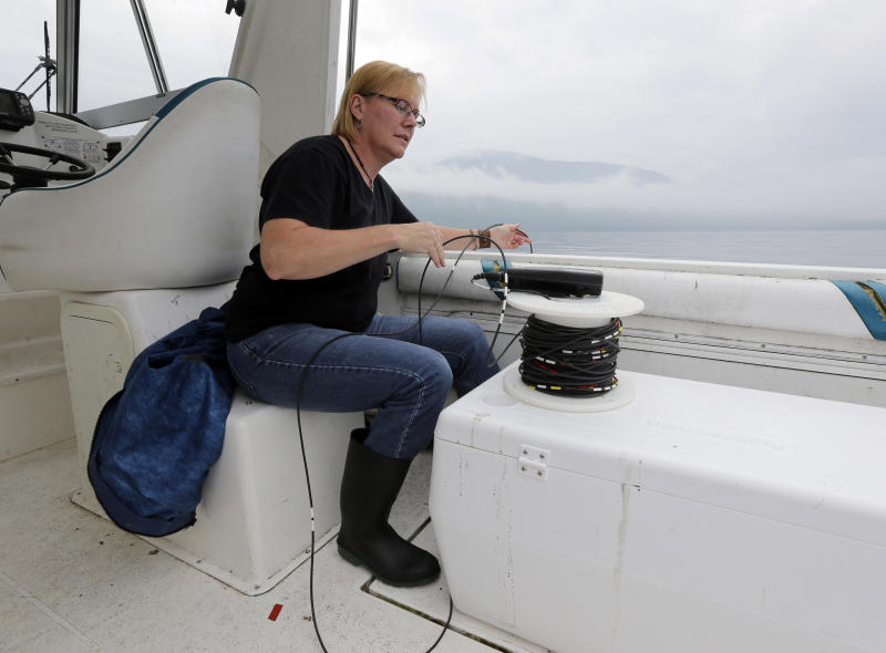 """Laurie Ahrens, a researcher for Rensselaer Polytechnic Institute's Darrin Fresh Water Institute, measures water temperature and oxygen levels on Lake George on Wednesday, June 26, 2013, in Bolton Landing, N.Y. An unprecedented project to turn New York's Lake George into the """"smartest lake in the world"""" is being launched to monitor the lake from its sun-dappled shores to its dark depths in hopes of keeping the Adirondack attraction pristine. (AP Photo/Mike Groll)"""