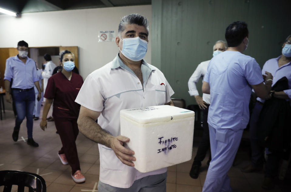 Nurse Gustavo Rodriguez carries a cooler of Russia's Sputnik V vaccine for COVID-19 which he will administer to fellow health workers at Dr. Pedro Fiorito Hospital in Avellaneda, Argentina, Tuesday, Dec. 29, 2020. (AP Photo/Natacha Pisarenko)