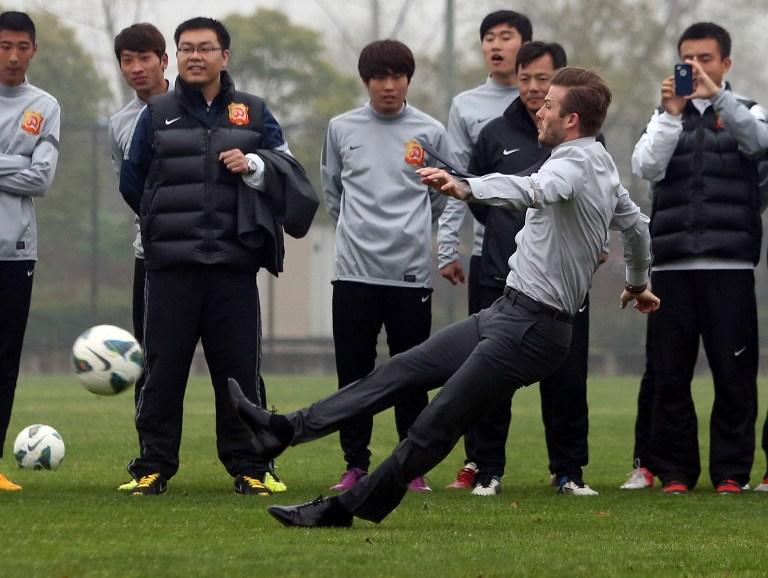 'Football superstar David Beckham (front R) illustrates a free kick before falling down on the pitch during a visit to the Zall Football Club in Wuhan, central China's Wuhan province on March 23, 2013. Beckham raised the prospect of one last stop on his global football journey on March 20, refusing to rule out playing in China after his contract with Paris Saint-Germain ends. CHINA OUT AFP PHOTO