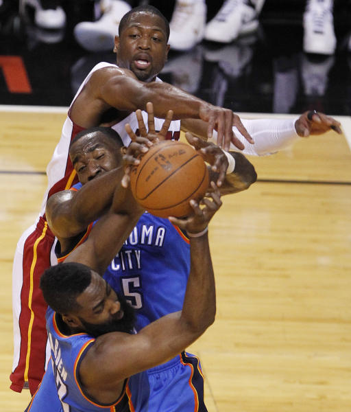 Miami Heat shooting guard Dwyane Wade (3), Oklahoma City Thunder center Kendrick Perkins (5) and guard James Harden (13) go after a rebound during the first half of Game 4 of the NBA Finals basketball series, Tuesday, June 19, 2012, in Miami. (AP Photo/Wilfredo Lee)
