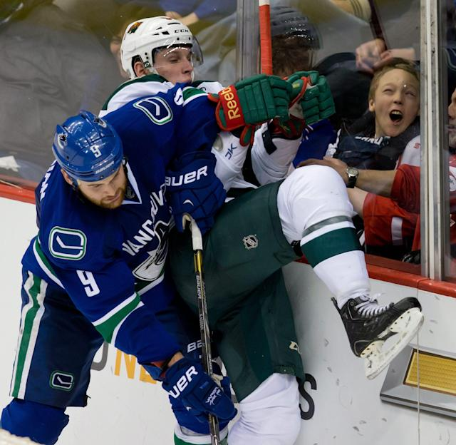 A young fan reacts as Vancouver Canucks' Zack Kassian, left, checks Minnesota Wild's Erik Haula during the second period of an NHL hockey game Friday, Feb. 28, 2014, in Vancouver, British Columbia. (AP Photo/The Canadian Press, Darryl Dyck)
