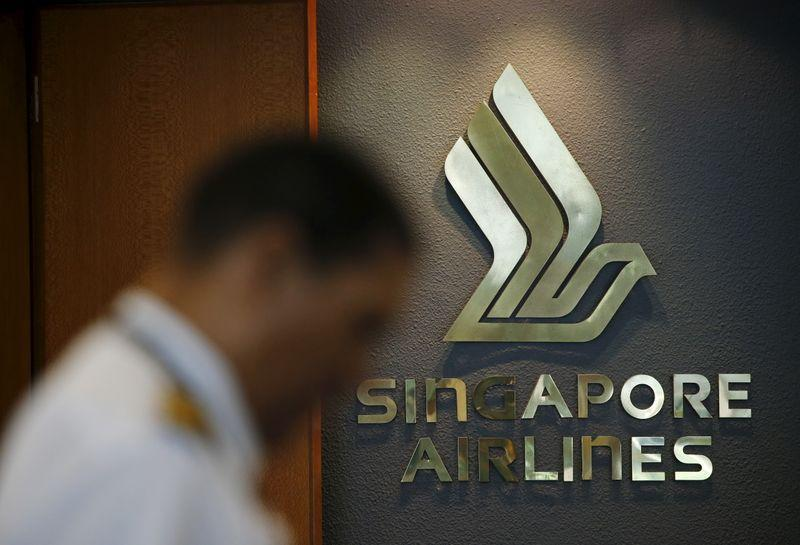 A flight crew passes a Singapore Airlines logo at Singapore's Changi Airport
