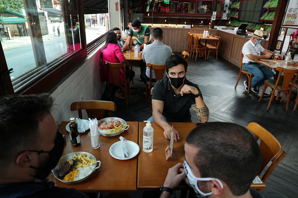 Customers sit in chairs at the tables arranged for maintaining social distance between guests at a dining room of a restaurant, as the city eases the restrictions imposed to control the spread of the coronavirus disease (COVID-19) in Sao Paulo, Brazil July 6, 2020. REUTERS/Amanda Perobelli