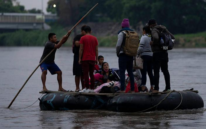 Migrants and travelers cross the Suchiate River, that marks the border between Guatemala and Mexico, on Sunday, June 6, 2021. - Moises Castillo/AP