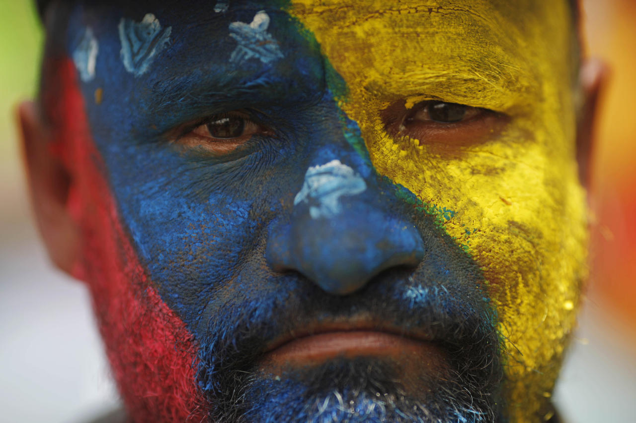¹A supporter of Venezuela's acting President Nicolas Maduro stands with his face painted in the colors of his nation's flag outside the national electoral council where Maduro registers his candidacy for president to replace late President Hugo Chavez in Caracas, Venezuela, Monday, March 11, 2013. Presidential elections were announced to take place on April 14, after Maduro announced on March 5 that Chavez had died. (AP Photo/Rodrigo Abd)