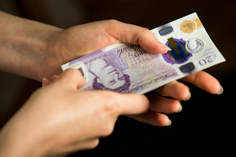 UNITED KINGDOM - 2020/06/06: In this photo illustration banknotes of the pound sterling, The Bank of England £20 notes with the image of Queen Elizabeth II are seen in a woman's hand. (Photo Illustration by Karol Serewis/SOPA Images/LightRocket via Getty Images)