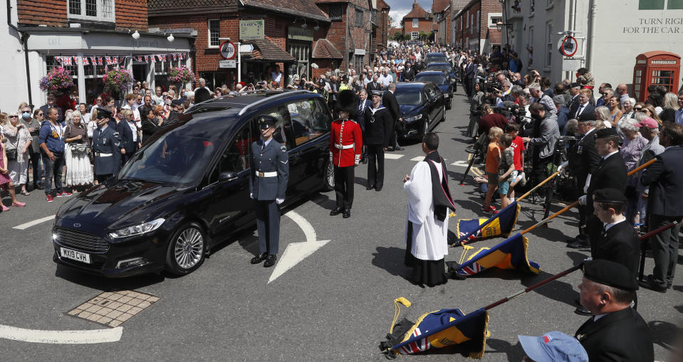 British singer and World War II icon Vera Lynn's funeral cortege is led through the village of Ditchling, southern England Friday, July 10, 2020. The cortege bearing Dame Vera will pause at the crossroads in the centre of Ditchling to acknowledge her long and happy 50 year association with the village and to allow residents to pay their respects. A flypast by the Battle of Britain Memorial Flight, consisting of a Spitfire and a Hurricane will take place during the pause at twelve noon, overhead the center of the village.(AP Photo/Alastair Grant)