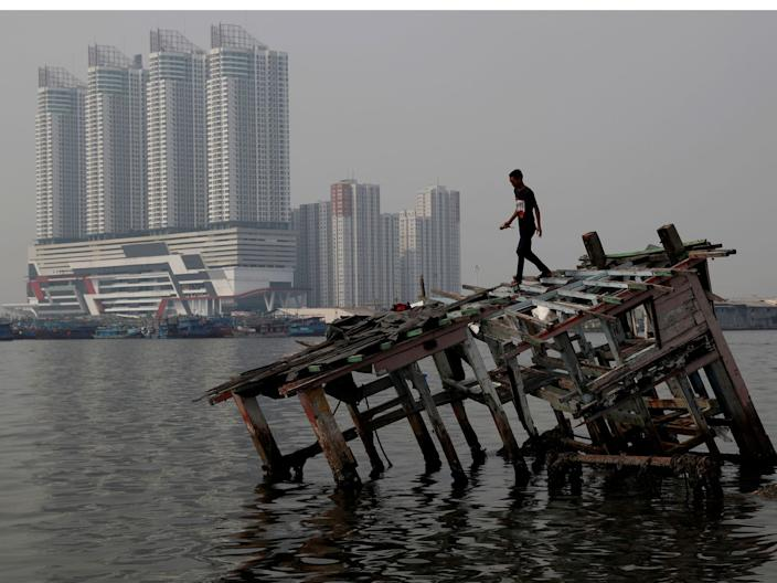 Pollution coronavirus A combination picture shows a man walking on top of the wreckage of a wooden boat, as smog covers the sky, July 26, 2018, (top) and a view of the same location pictured during the coronavirus disease (COVID-19) outbreak, in North Jakarta, Indonesia