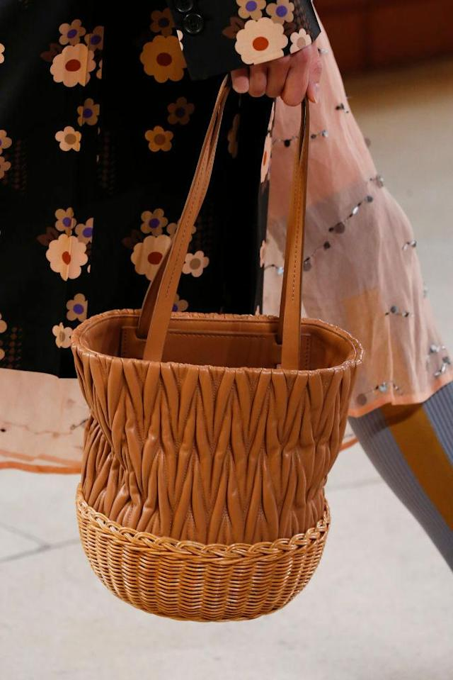 <p>A model carries a brown bucket basket bag during the Miu Miu spring/summer 2018 show in Paris. (Photo: Getty Images) </p>