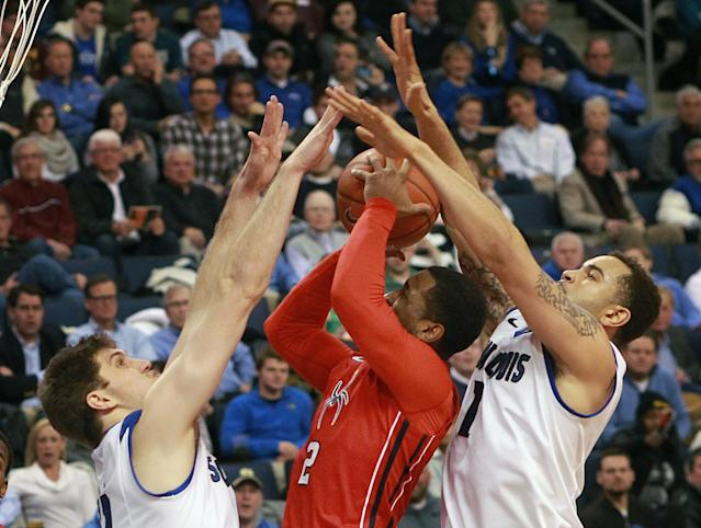 Saint Louis University forwards Rob Loe, left, and Grandy Glaze collapse on Richmond guard Cedrick Lindsay during the second half of an NCAA basketball game, Wednesday, Jan. 29, 2014 in St. Louis. (AP Photo/St. Louis Post-Dispatch, Chris Lee)