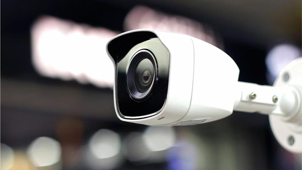 A standard CCTV camera is seen wall-mounted against a blurred background of lights