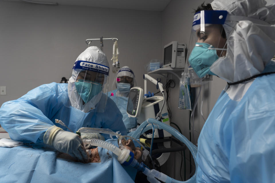 Medical staff members treat a patient suffering from the coronavirus disease (COVID-19) in the COVID-19 intensive care unit (ICU) at the United Memorial Medical Center (UMMC) on October 31, 2020 in Houston, Texas. (Go Nakamura/Getty Images)
