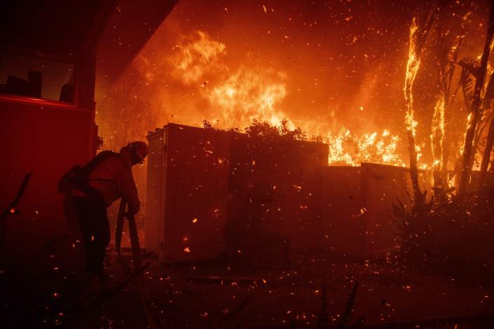 Firefighters try to save a home on Tigertail Road from the Getty fire, Oct. 28, 2019, in Los Angeles, Calif. (Photo: Christian Monterrosa/AP)