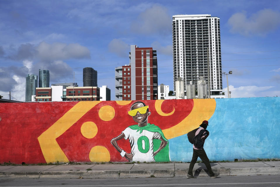 The skyline of downtown Miami stands behind a mural painted by artist Kyle Holbrook in the Overtown neighborhood of Miami, Wednesday, June 2, 2021. (AP Photo/Lynne Sladky)