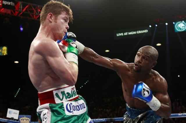 WBC/WBA 154-pound champion Canelo Alvarez (L) avoids a punch from Floyd Mayweather Jr. of the U.S. at the MGM Grand Garden Arena in Las Vegas, Nevada, September 14, 2013. REUTERS/Steve Marcus (UNITED STATES - Tags: SPORT BOXING TPX IMAGES OF THE DAY)