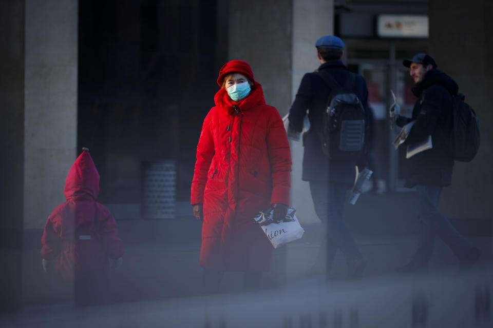 A woman wearing a face mask to help curb the spread of the coronavirus walks into the underpass under the street during sunset in Moscow, Russia, Wednesday, Dec. 2, 2020. Russia has registered a record number of coronavirus deaths for a second straight day. Currently, there is a country-wide mask mandate and mostly mild restrictions that vary from region to region. (AP Photo/Alexander Zemlianichenko)