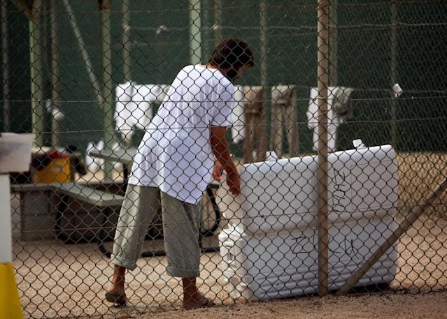 GUANTANAMO BAY, CUBA - JANUARY 21: (NOTE TO EDITORS: PHOTO HAS BEEN REVIEWED BY US MILITARY OFFICIALS) A Guantanamo detainee opens a cooler inside the open yard at Camp 4 detention center at the U.S. Naval Base January 21, 2009 in Guantanamo Bay, Cuba. The Guantanamo Bay war crimes court came to an abrupt halt today as military judges granted President Barack Obama's request to suspend proceedings while he reviews his predecessor's strategy for prosecuting terrorists. (Photo by Brennan Linsley-Pool/Getty Images)