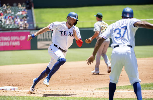 Texas Rangers' Hunter Pence is waved home by third base coach Tony Beasley (37) on his way to scoring on a single by Asdrubal Cabrera off of Oakland Athletics starting pitcher Paul Blackburn during the first inning of the first baseball game of a doubleheader Saturday, June 8, 2019, in Arlington, Texas. Elvis Andrus also scored on the play. (AP Photo/Jeffrey McWhorter)