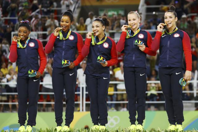 2016 Rio Olympics - Artistic Gymnastics - Final - Women's Team Final - Rio Olympic Arena - Rio de Janeiro, Brazil - 09/08/2016. (L-R) Simone Biles (USA) of USA, Gabrielle Douglas (USA) of USA (Gabby Douglas), Laurie Hernandez (USA) of USA, Madison Kocian (USA) of USA, Alexandra Raisman (USA) of USA (Aly Raisman) bite their gold medals on the podium after winning the women's team final. REUTERS/Mike Blake FOR EDITORIAL USE ONLY. NOT FOR SALE FOR MARKETING OR ADVERTISING CAMPAIGNS.