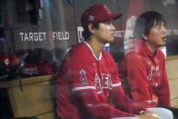 Los Angeles Angels' Shohei Ohtani, left, and his interpreter watch the sixth inning from the dugout as Ohtani did not play against the Minnesota Twins in a baseball game Friday, July 23, 2021, in Minneapolis. The Twins won 5-4. (AP Photo/Jim Mone)