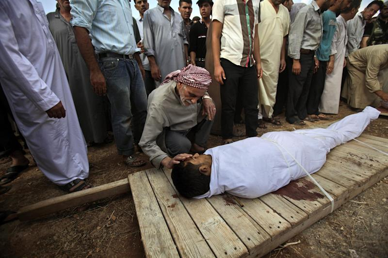 A Syrian man touches the body of his son, Abdullah Al-Rayzour, 23, during a funeral for four men who were killed in a government airstrike in Marea, on the outskirts of Aleppo, Syria, Tuesday, Sept. 11, 2012. (AP Photo/Muhammed Muheisen)